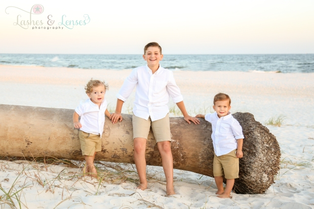 Three brothers standing by washed up palm tree on the beach at Johnsons Beach in Perdido Key