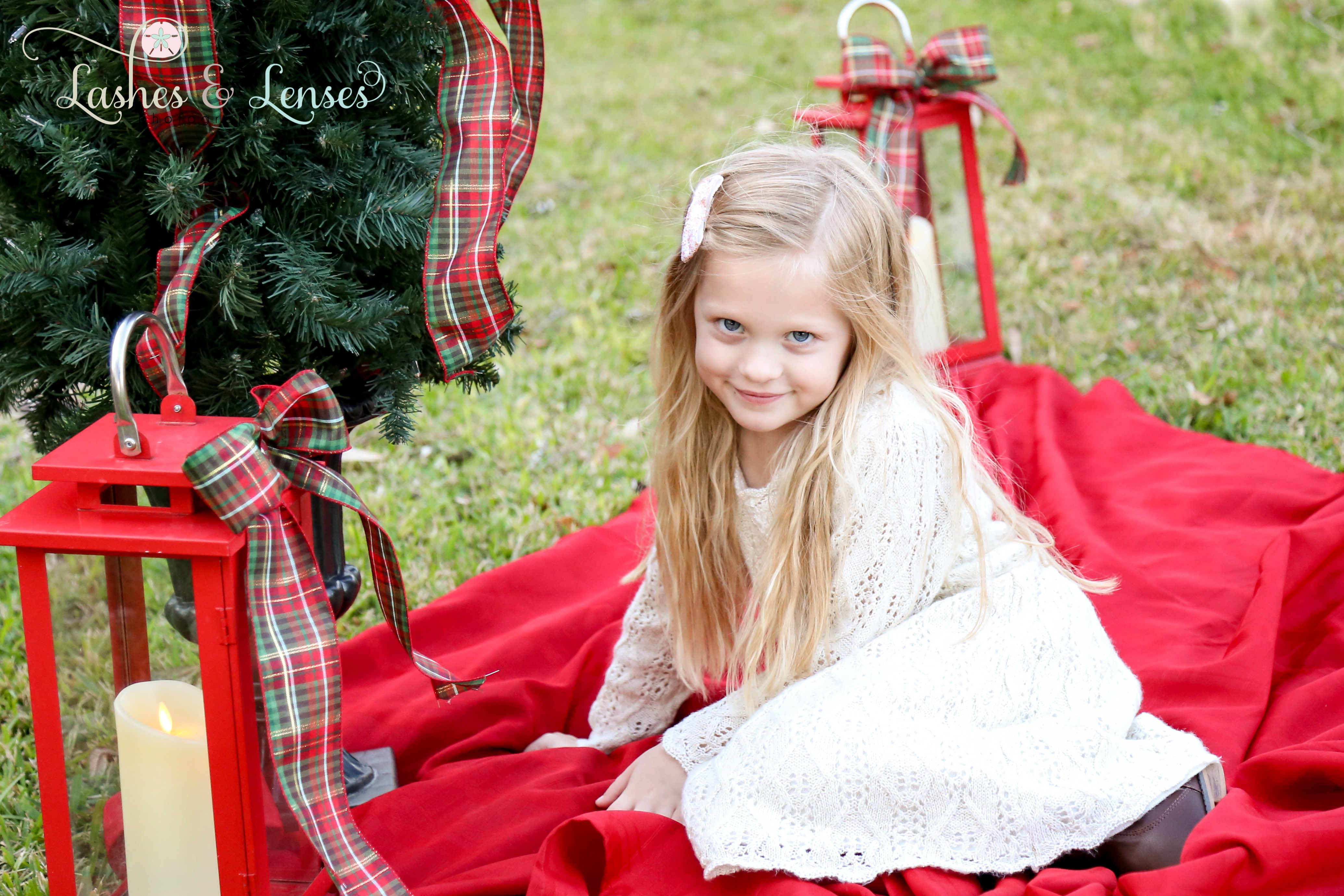 Little girl sitting on a blanket for Christmas card photos at Innerarity Point Park