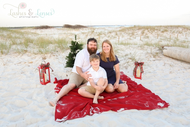 Mom and Dad sitting on red blanket with son for Christmas Photos at Johnsons Beach in Perdido Key