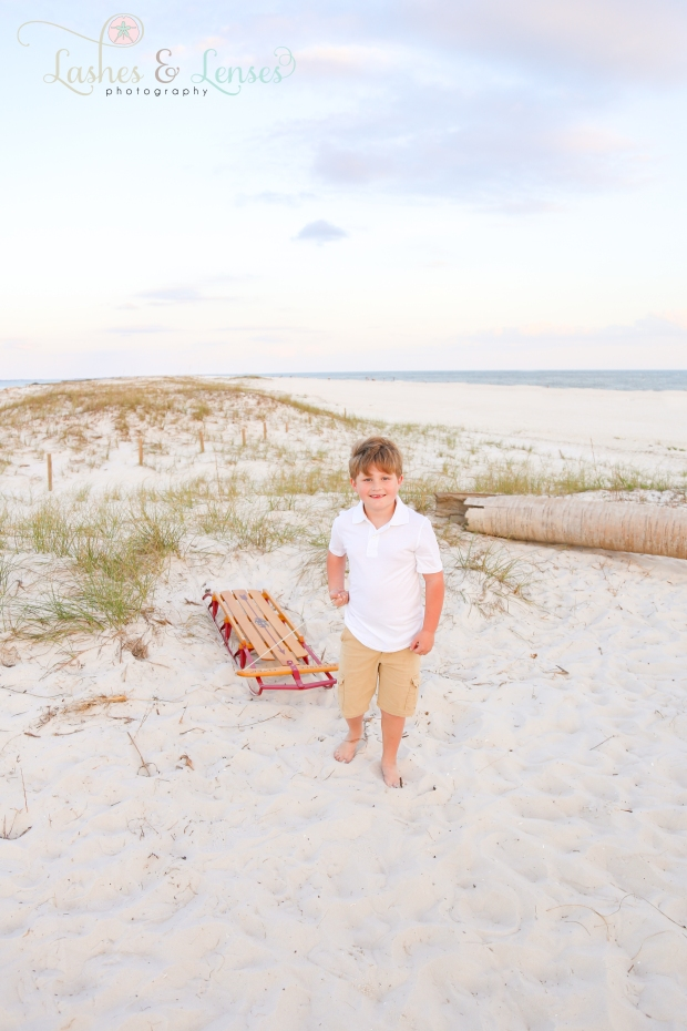 Little boy pulling sled in the sand for Christmas Photos at Johnsons Beach in Perdido Key
