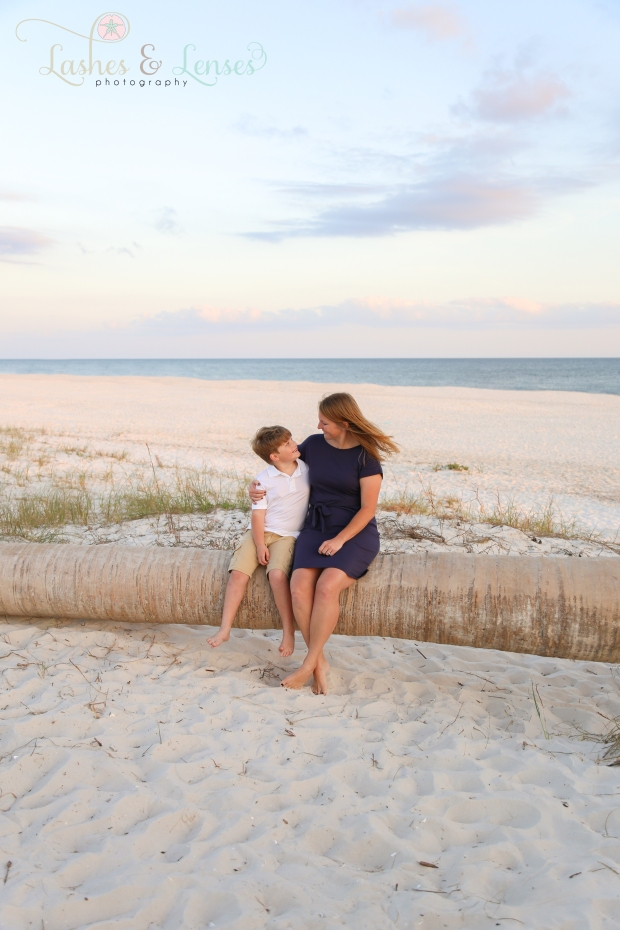 Mom sitting on washed up palm tree with son at Johnsons Beach in Perdido Key