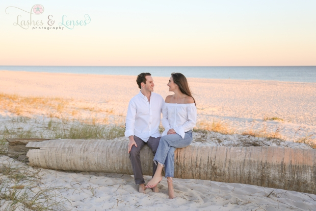 Young Couple sitting on washed up palm tree looking at each other at Johnsons Beach in Perdido Key