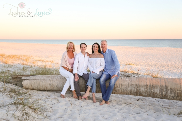 Family with adult children. sitting on washed up palm tree at Johnsons Beach in Perdido Key