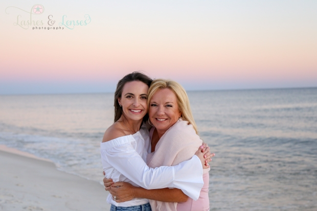 Mother and Daughter hugging standing next to the water at Johnsons Beach in Perdido Key