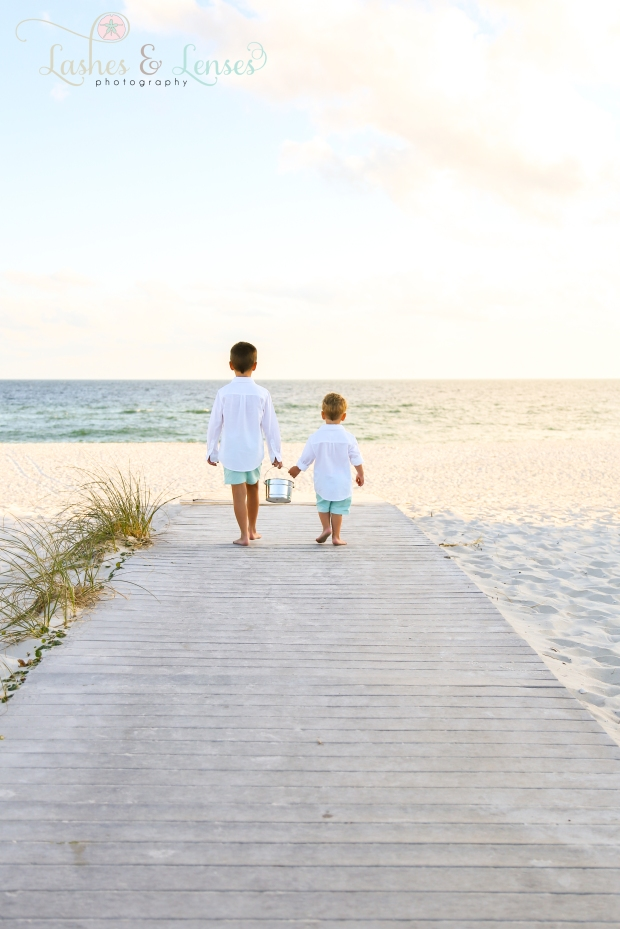 Young brothers looking out at the water while standing on the boardwalk at Johnsons Beach in Perdido Key
