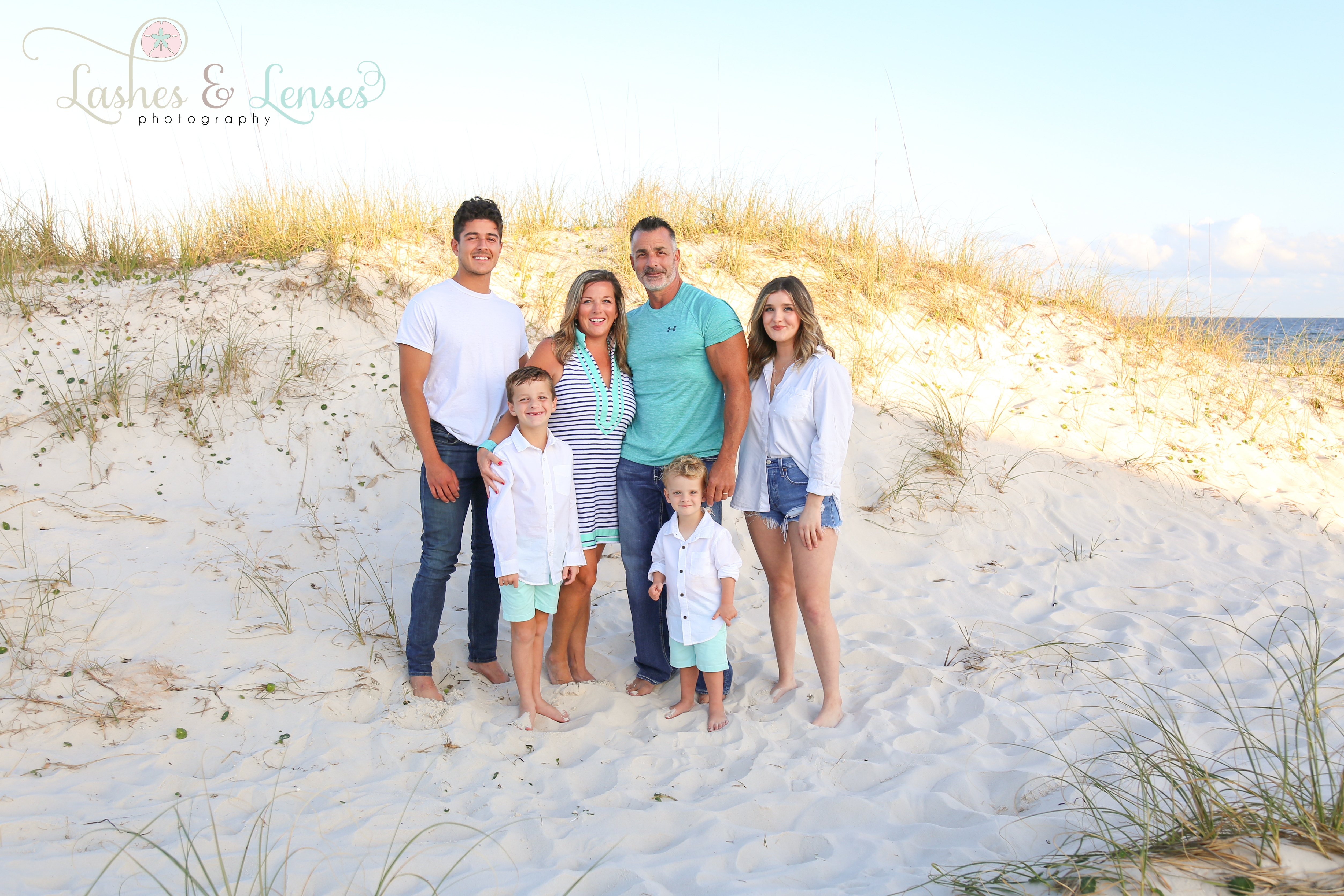 Family with teen children and young children standing next to the sand dunes at Johnsons Beach in Perdido Key