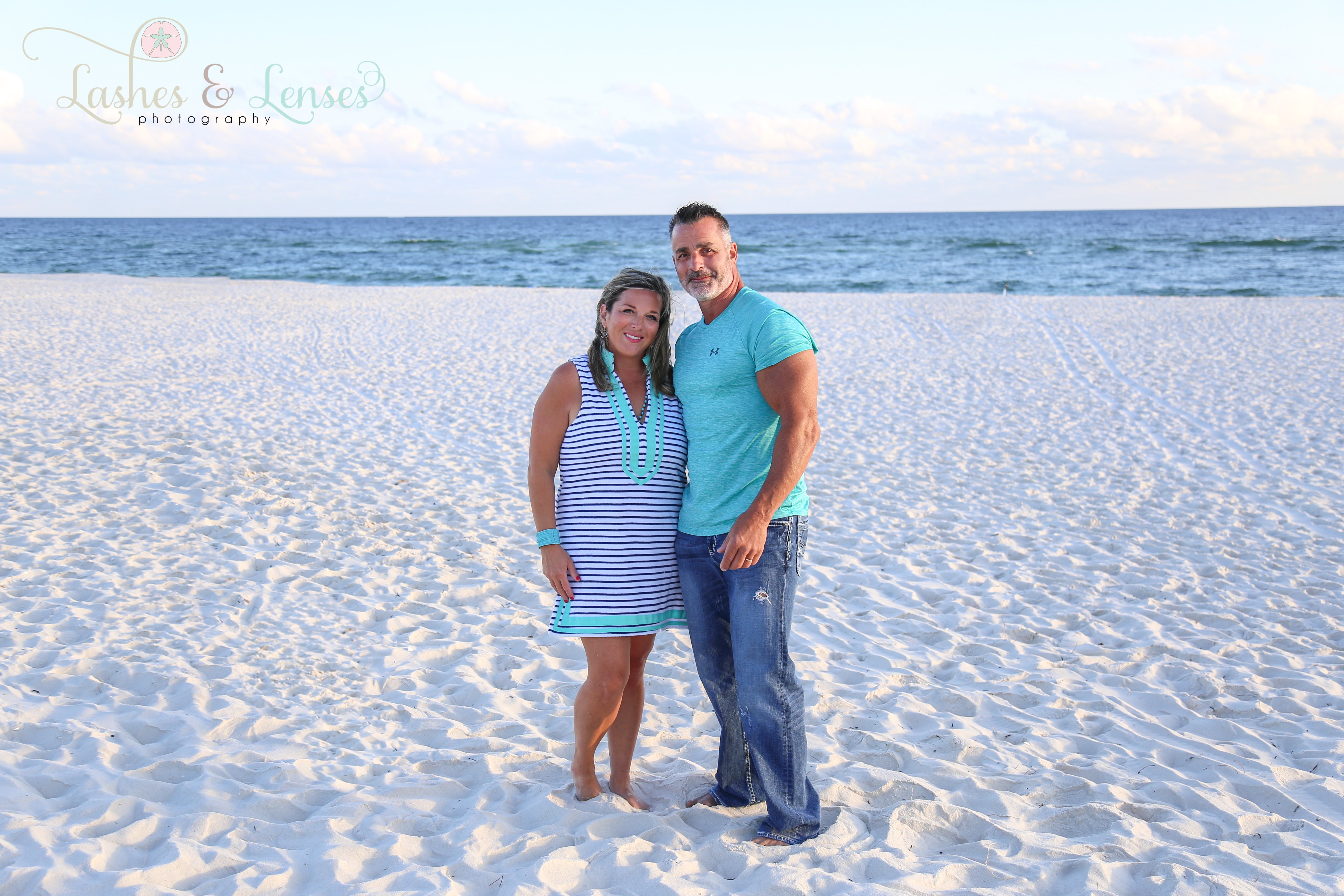 Couple with the gulf behind them looking at the camera at Johnsons Beach in Perdido Key