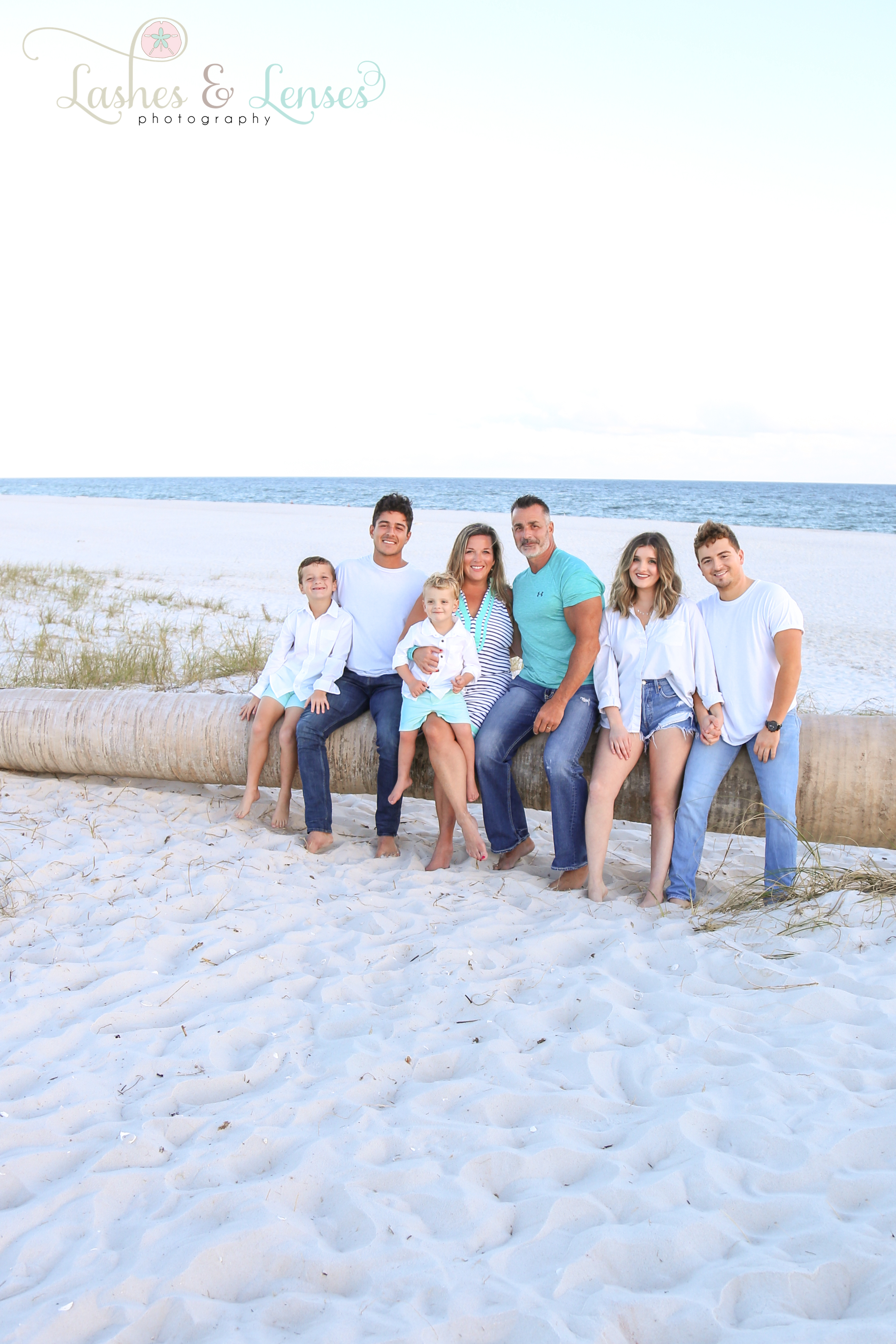 Family sitting on washed up palm tree at Johnsons Beach in Perdido Key