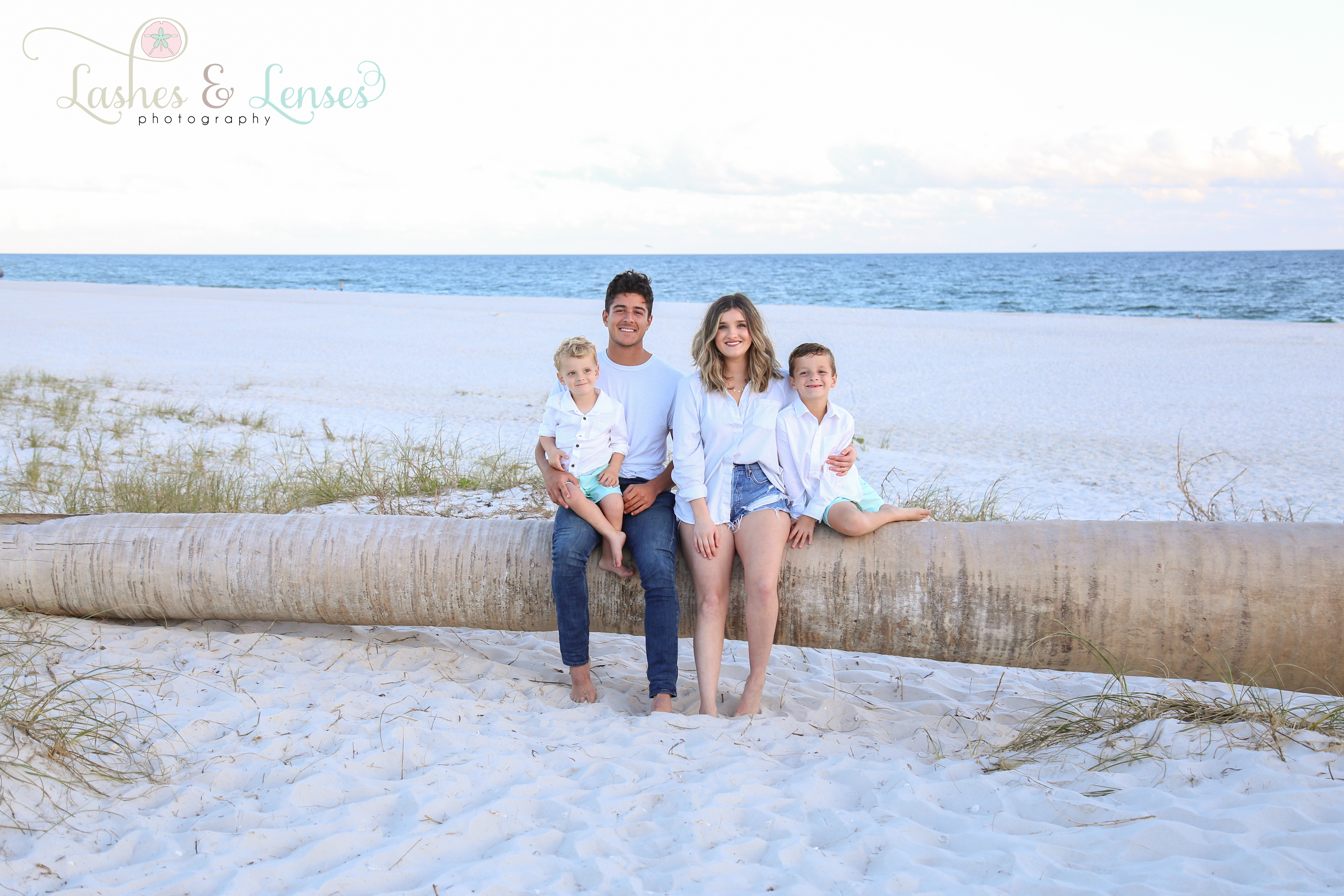Teen siblings with younger brothers sitting on washed up palm tree at Johnsons Beach in Perdido Key