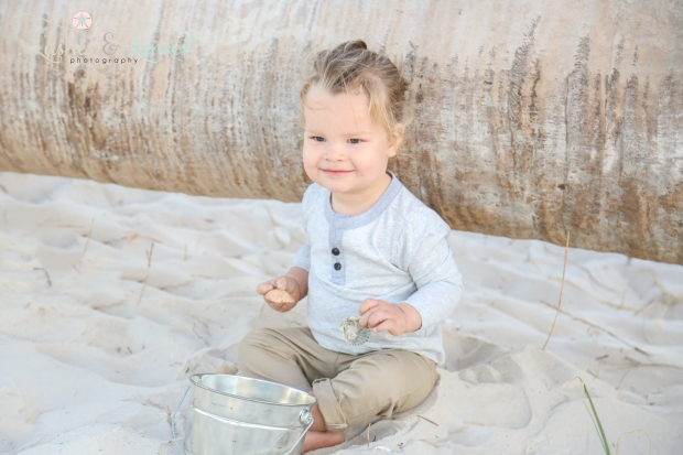 Toddler boy sitting on the beach next to a washed up log at Johnsons Beach in Perdido Key
