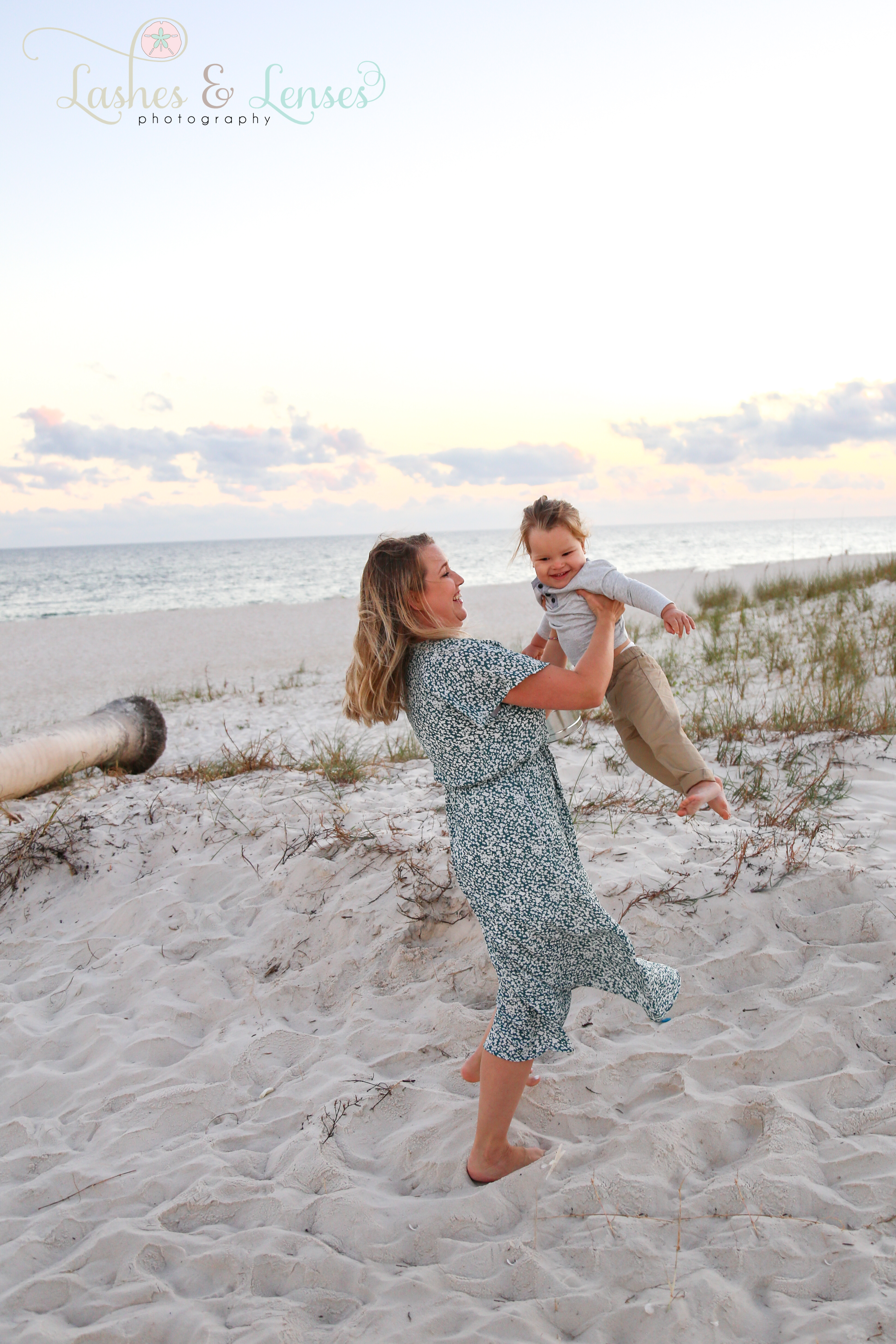 Mom swinging little boy in the air on the beach at Johnsons Beach in Perdido Key