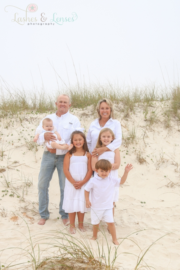 Grandparents with their grandchildren standing by the sand dunes at Johnsons Beach in Perdido Key
