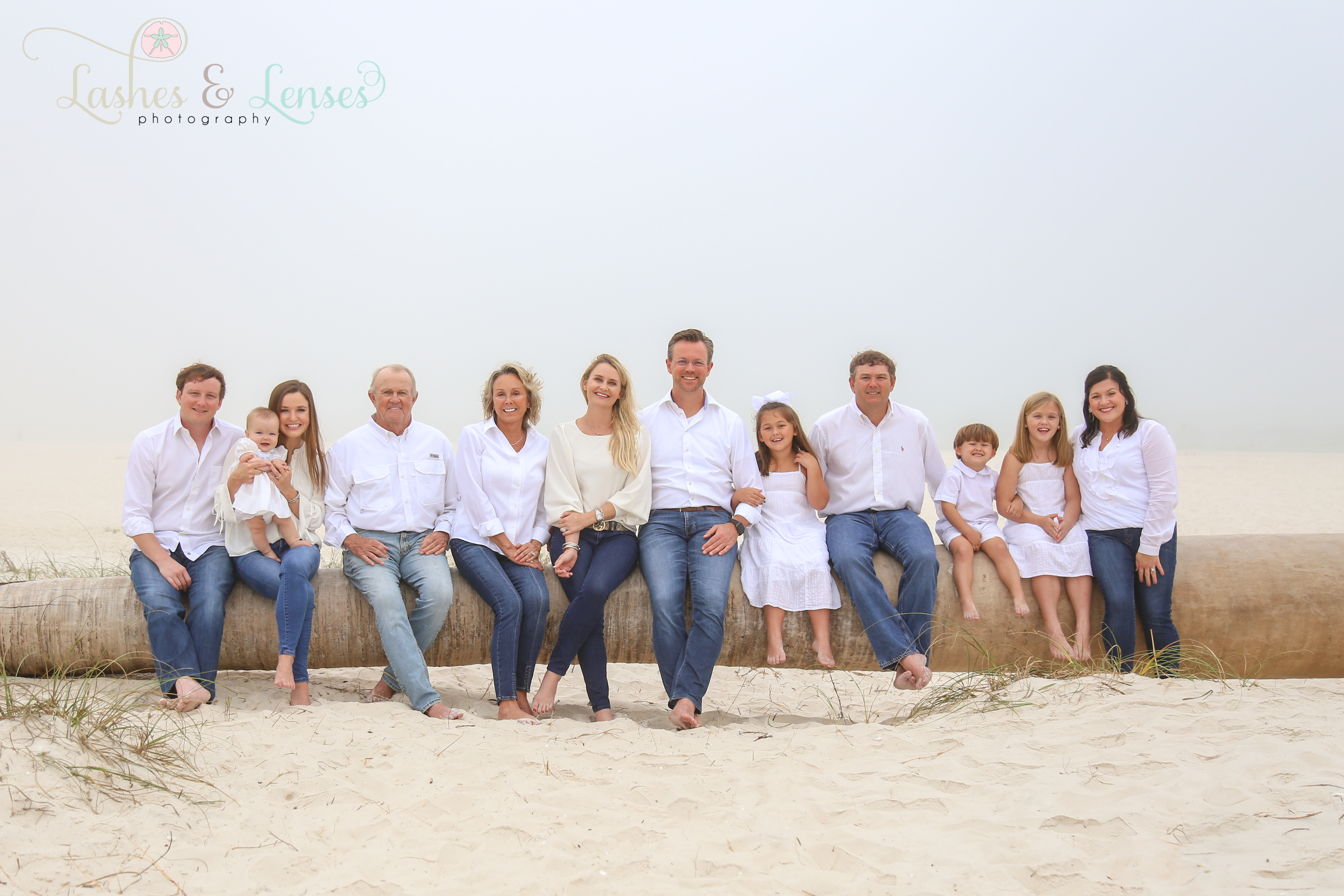 Large family sitting on a washed up palm tree on the beach at Johnsons Beach in Perdido Key