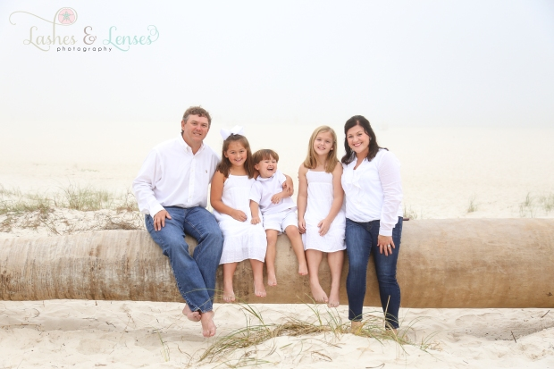 Mom and dad with two daughters and son  sitting on a washed up palm tree on the beach at Johnsons Beach in Perdido Key