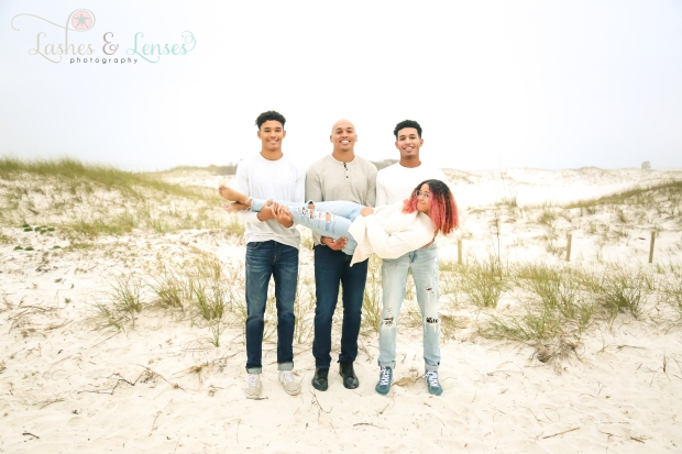 Brothers holding sister in the sand dunes at Johnsons Beach in Perdido Key