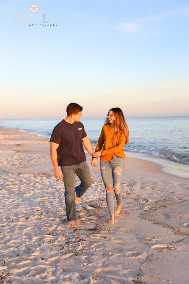 Newly engaged couple walking next to the water at Johnsons Beach in Perdido Key