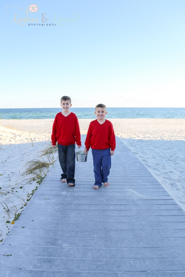 Brothers holding pail on boardwalk at Johnsons Beach in Perdido Key