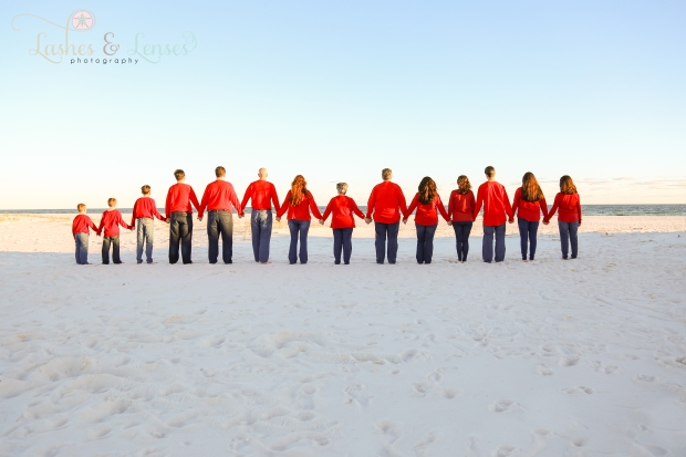 Large extended family standing in a line looking at the water at Johnsons Beach in Perdido Key
