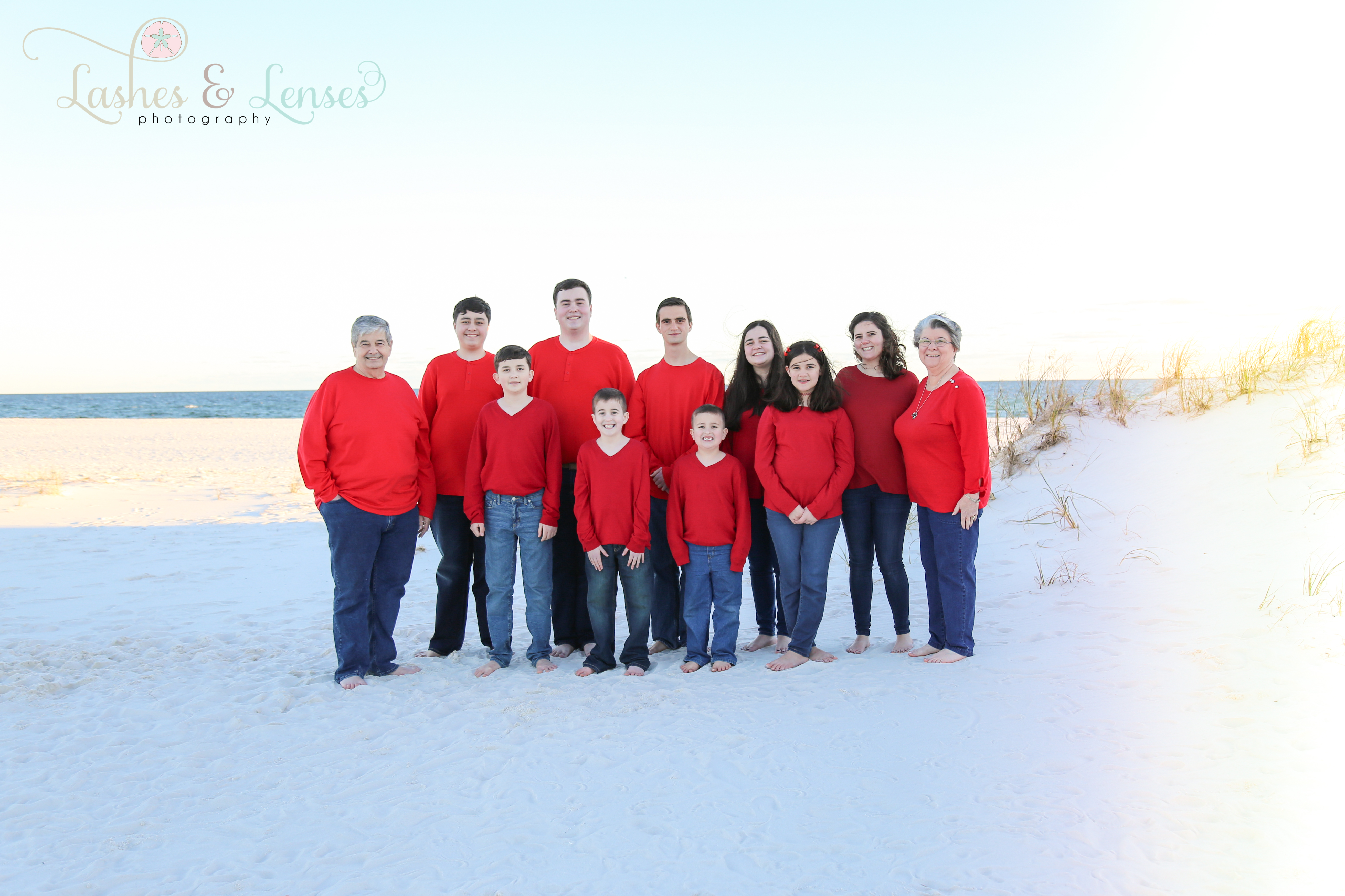 Grandparents with all their grandchildren with the water behind them at Johnsons Beach in Perdido Key