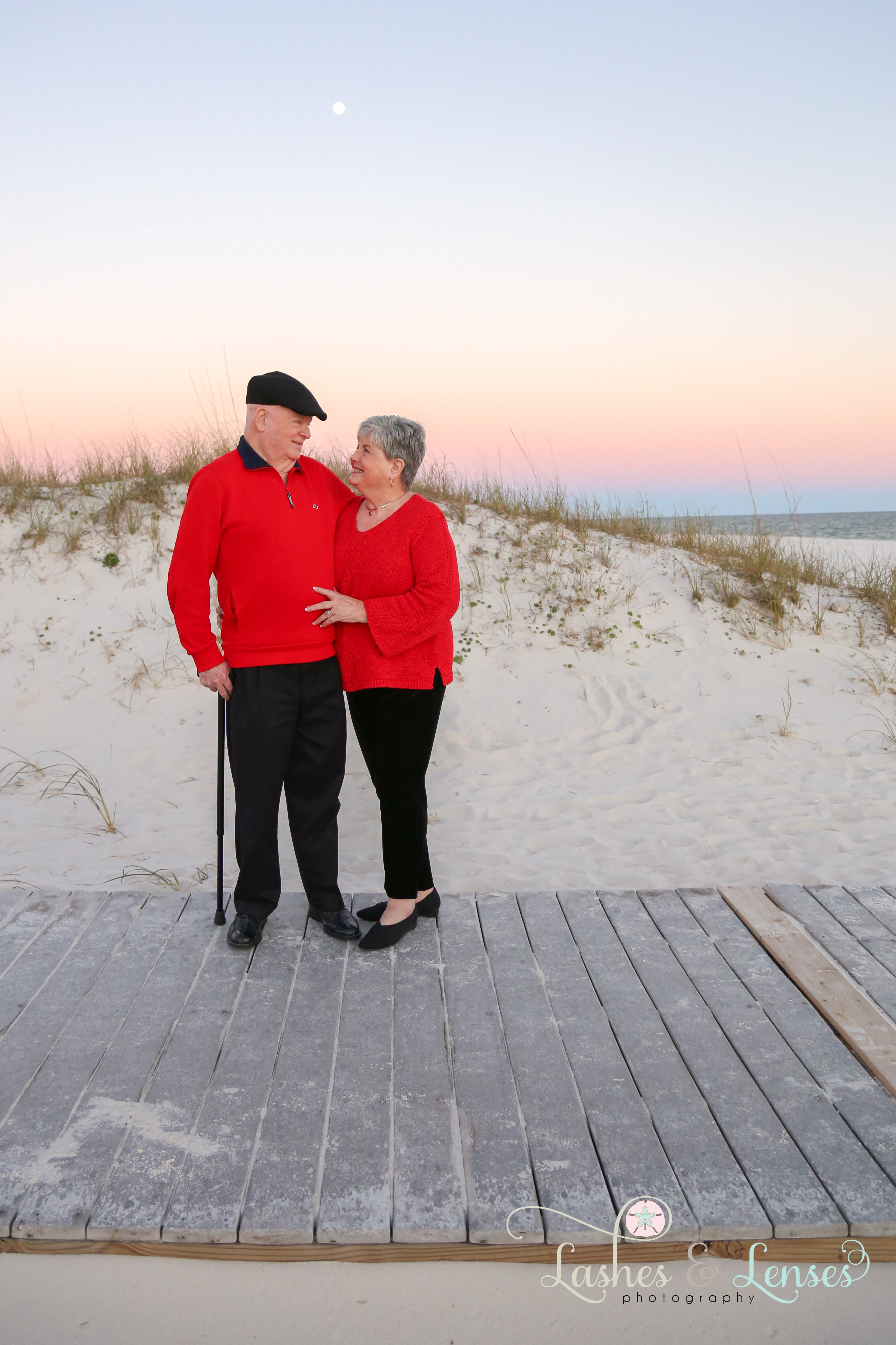 Mature couple standing on the boardwalk looking at each other at Johnsons Beach in Perdido Key