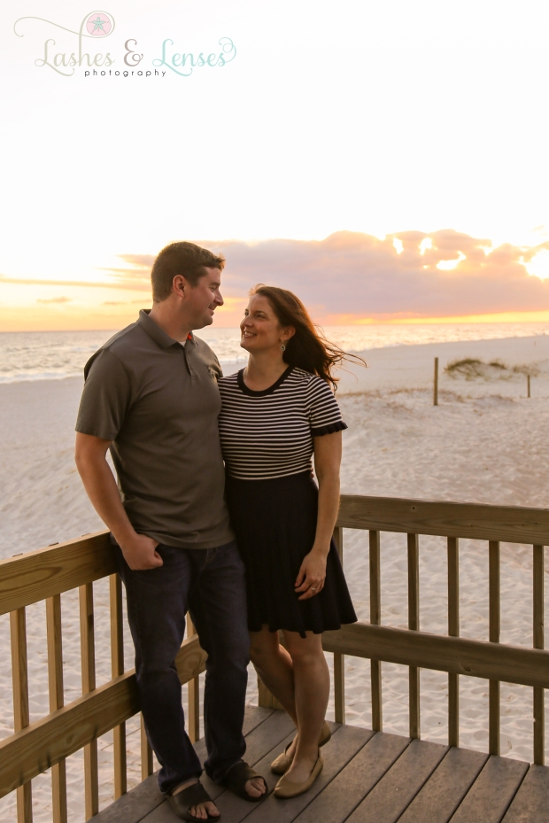 Couple standing on pavilion with sunset behind them at Johnsons Beach in Perdido Key