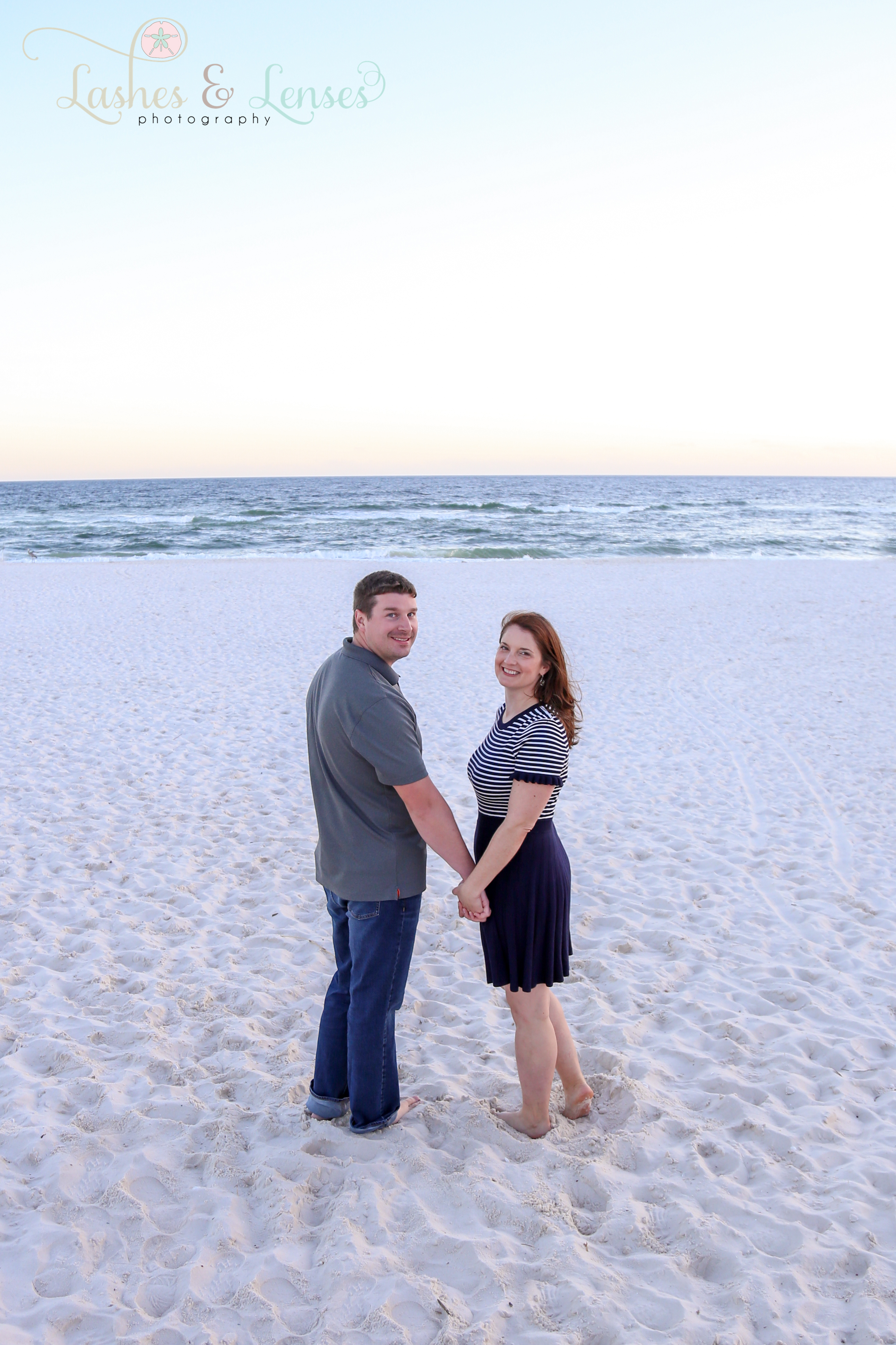 Couple standing on the beach with gulf behind them at Johnsons Beach in Perdido Key