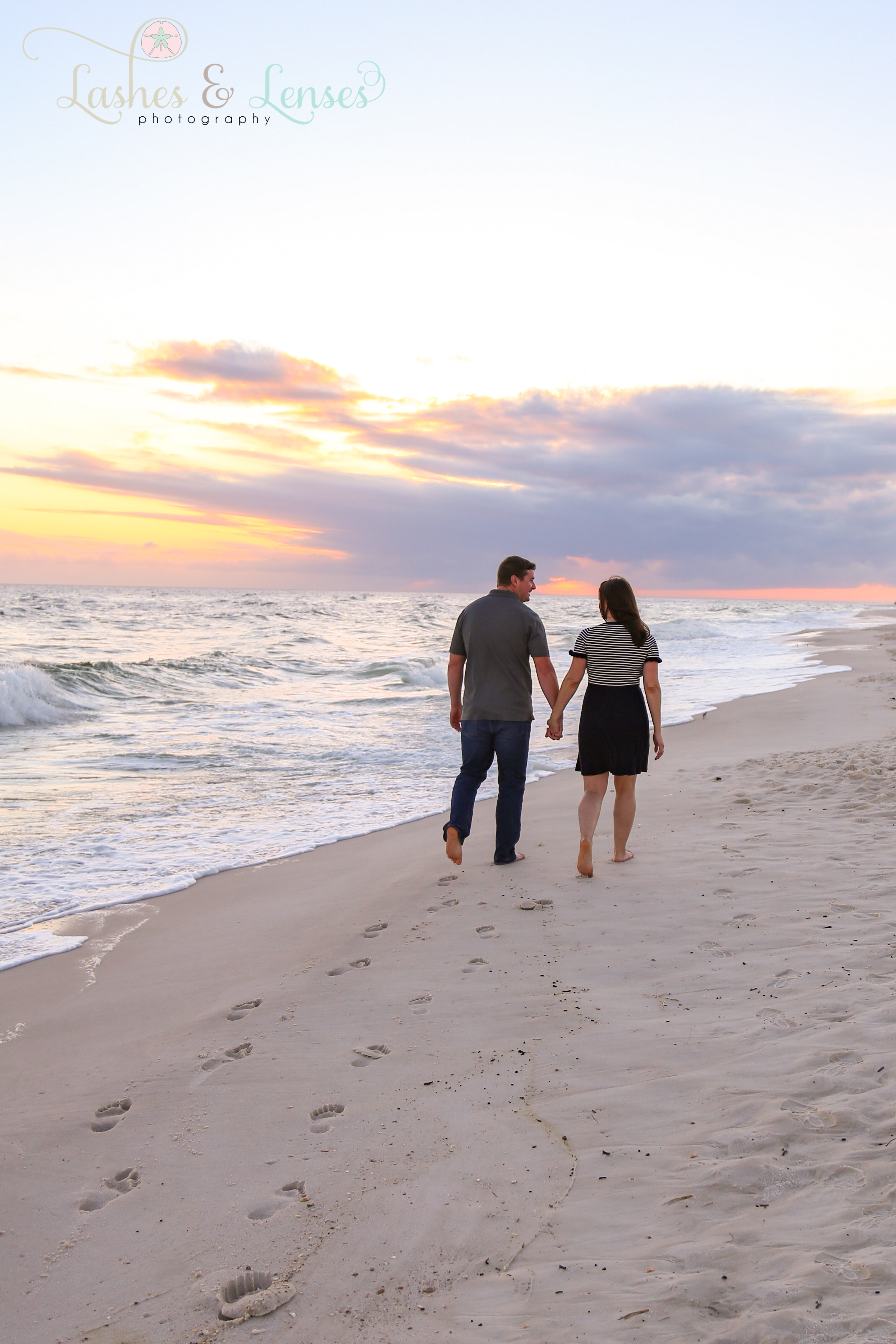 Couple walking down the beach with the sunset in front of them at Johnsons Beach in Perdido Key