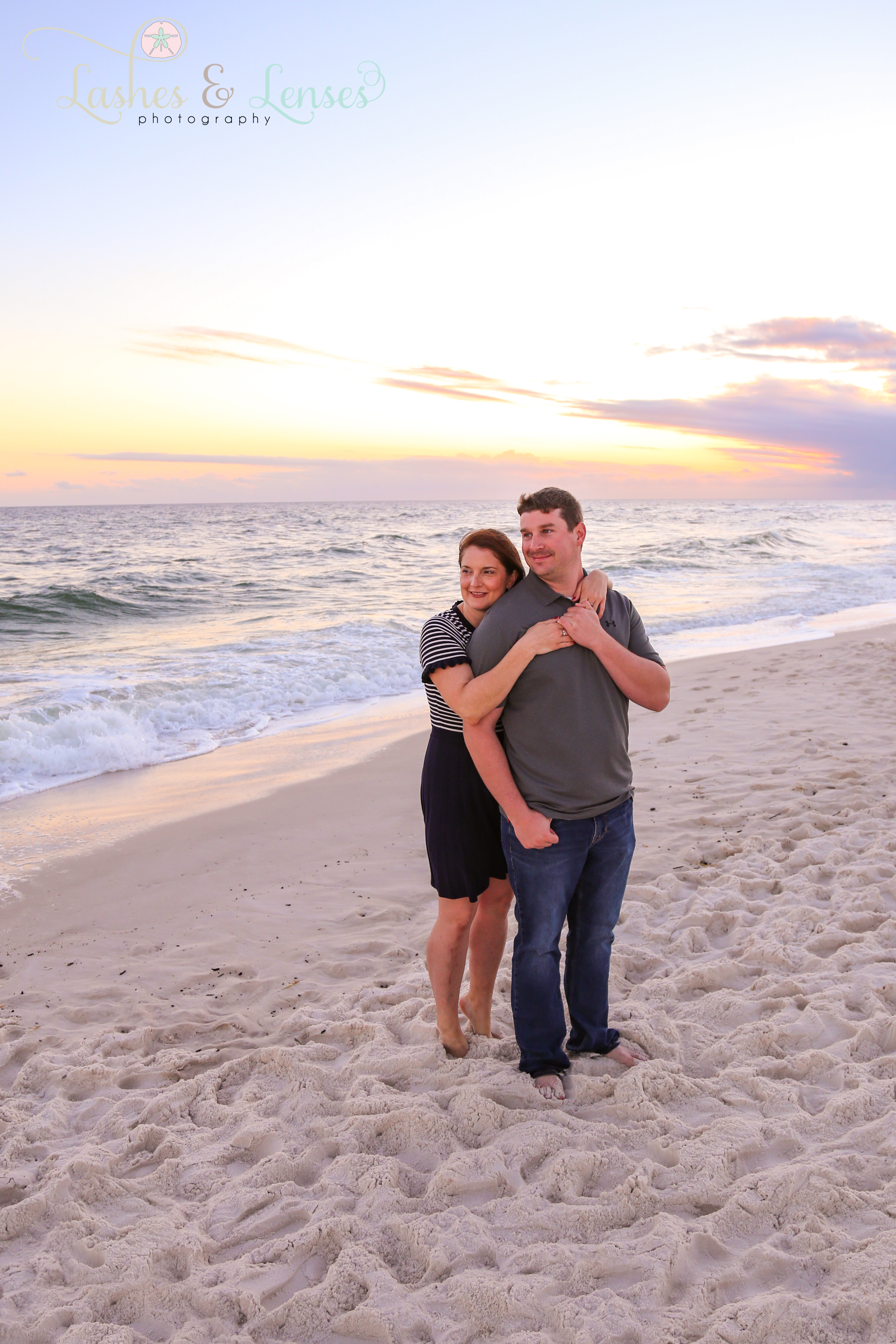 Couple embracing with the sunset behind them at Johnsons Beach in Perdido Key