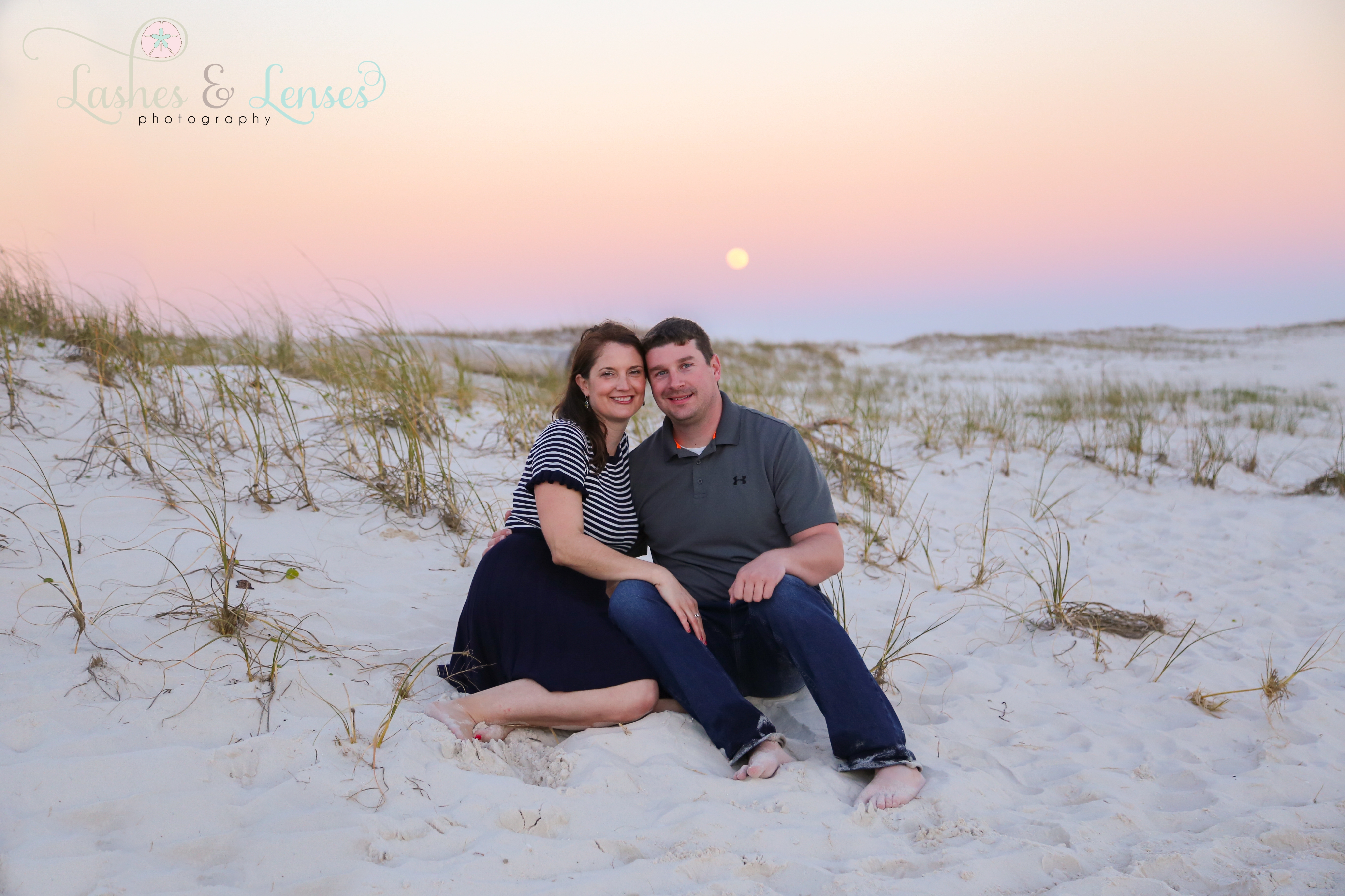 Couple sitting in the sand dunes with the last full moon of 2020 behind them at Johnsons Beach in Perdido Key