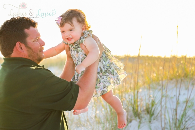 Grandpa throwing baby granddaughter in the air at Johnsons Beach in Perdido Key
