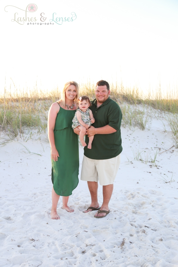 Family with baby daughter standing in the sand dunes at Johnsons Beach in Perdido Key