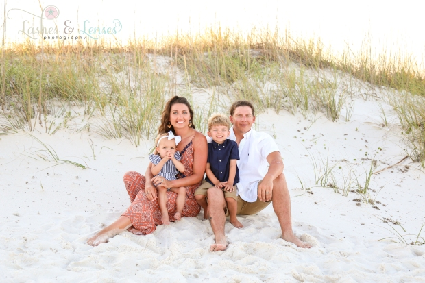 Family with their two small children sitting in front of the sand dunes at Johnsons Beach in Perdido Key