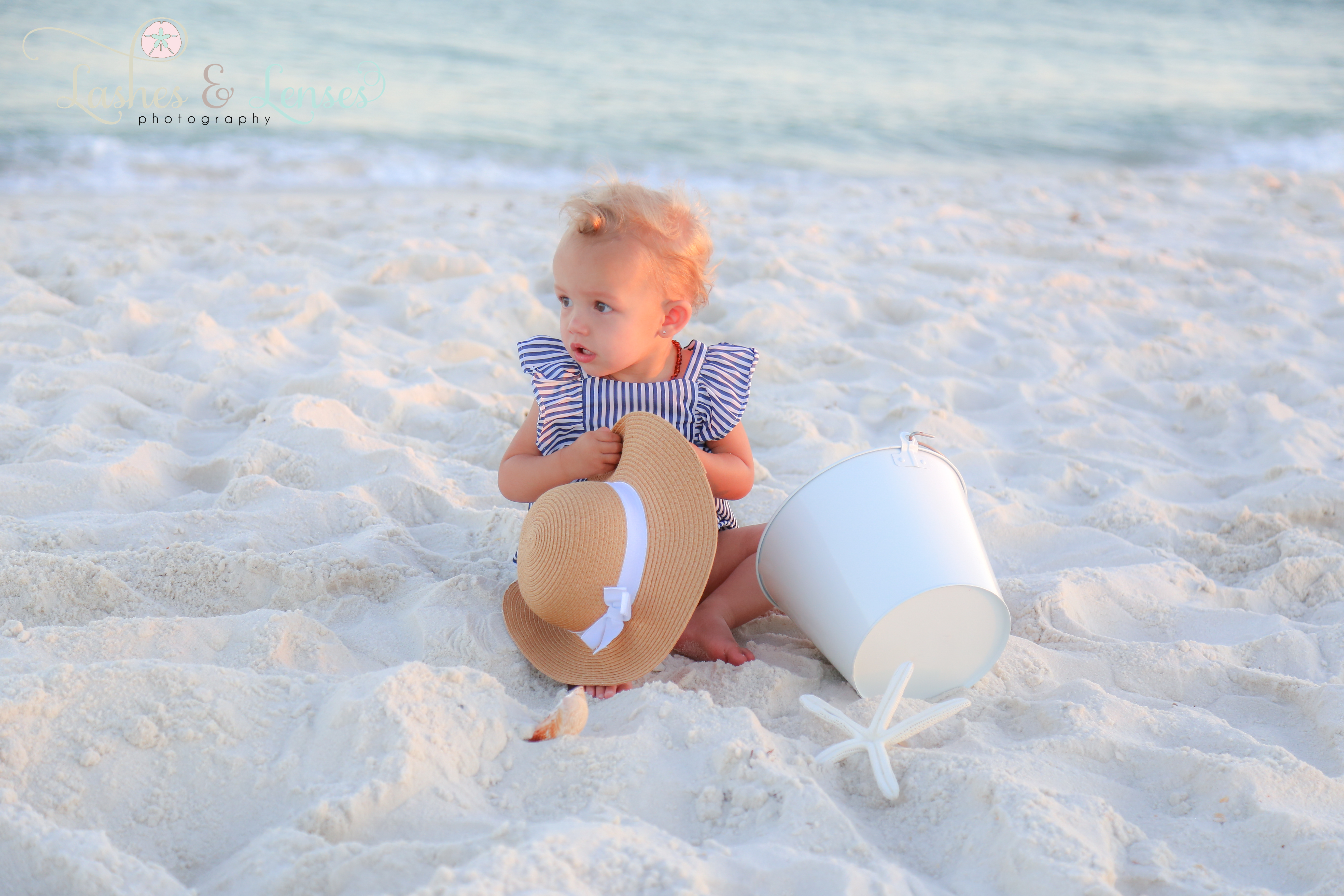 Small girl sitting in the sand in from of the water at Johnsons Beach in Perdido Key