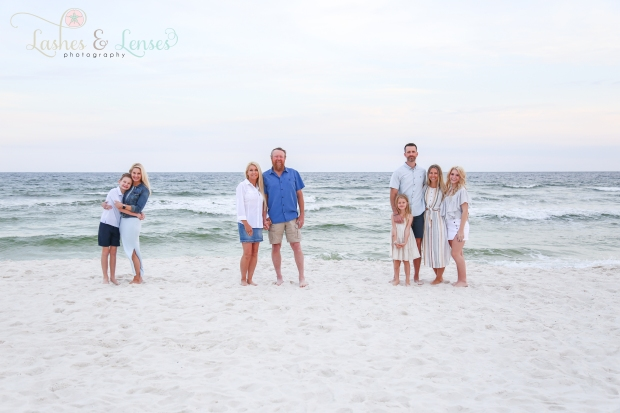 Large family in groups by the edge of the water at Johnsons Beach in Perdido Key
