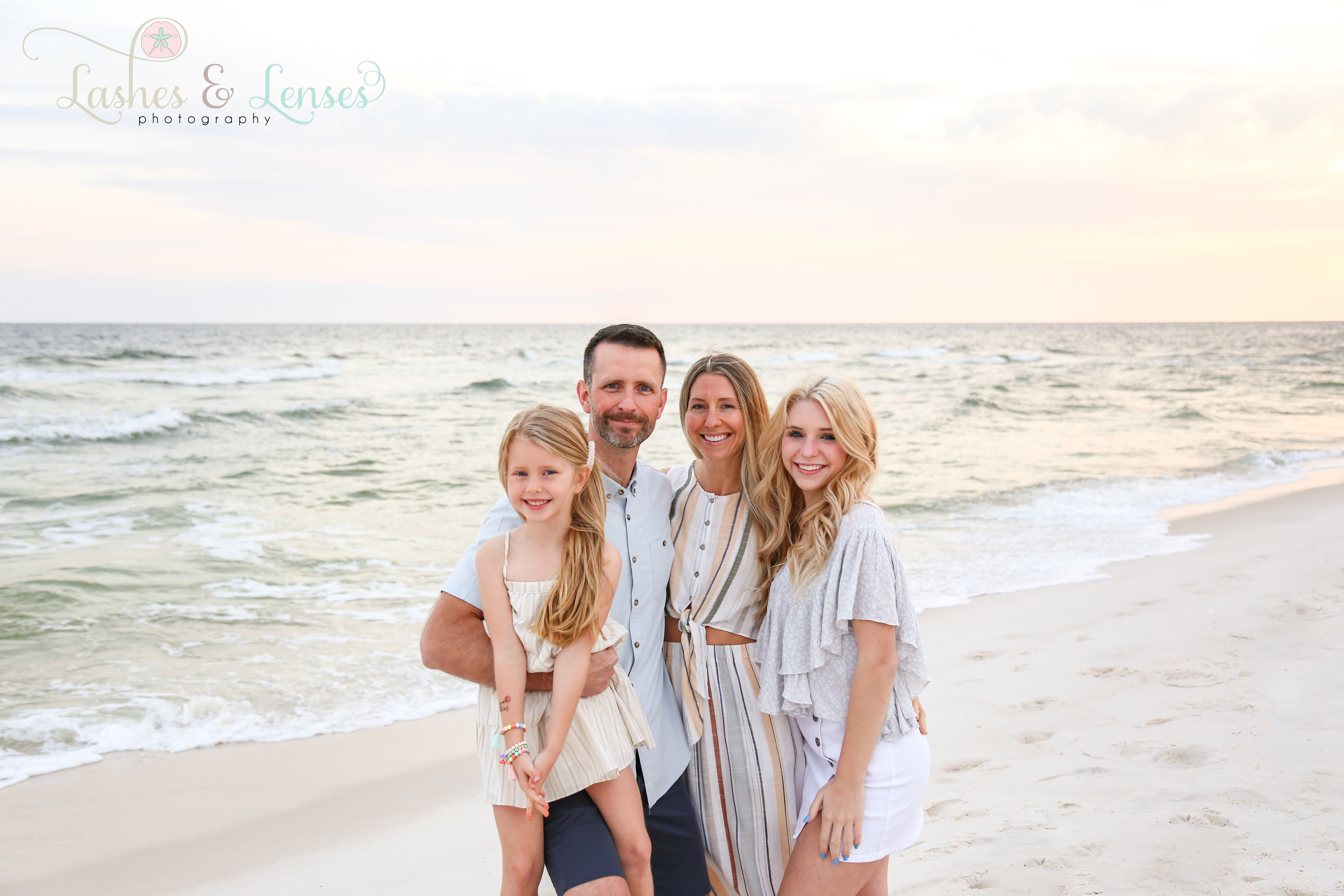 Husband and wife with two daughters by the water at Johnsons Beach in Perdido Key