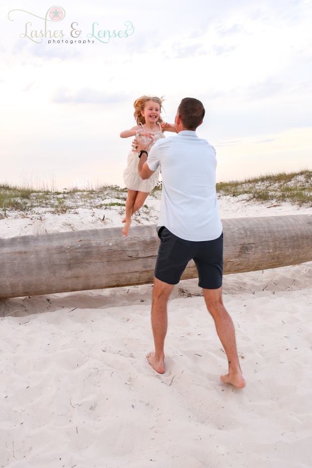 little girl jumping off tree into dads arms at Johnsons Beach in Perdido Key