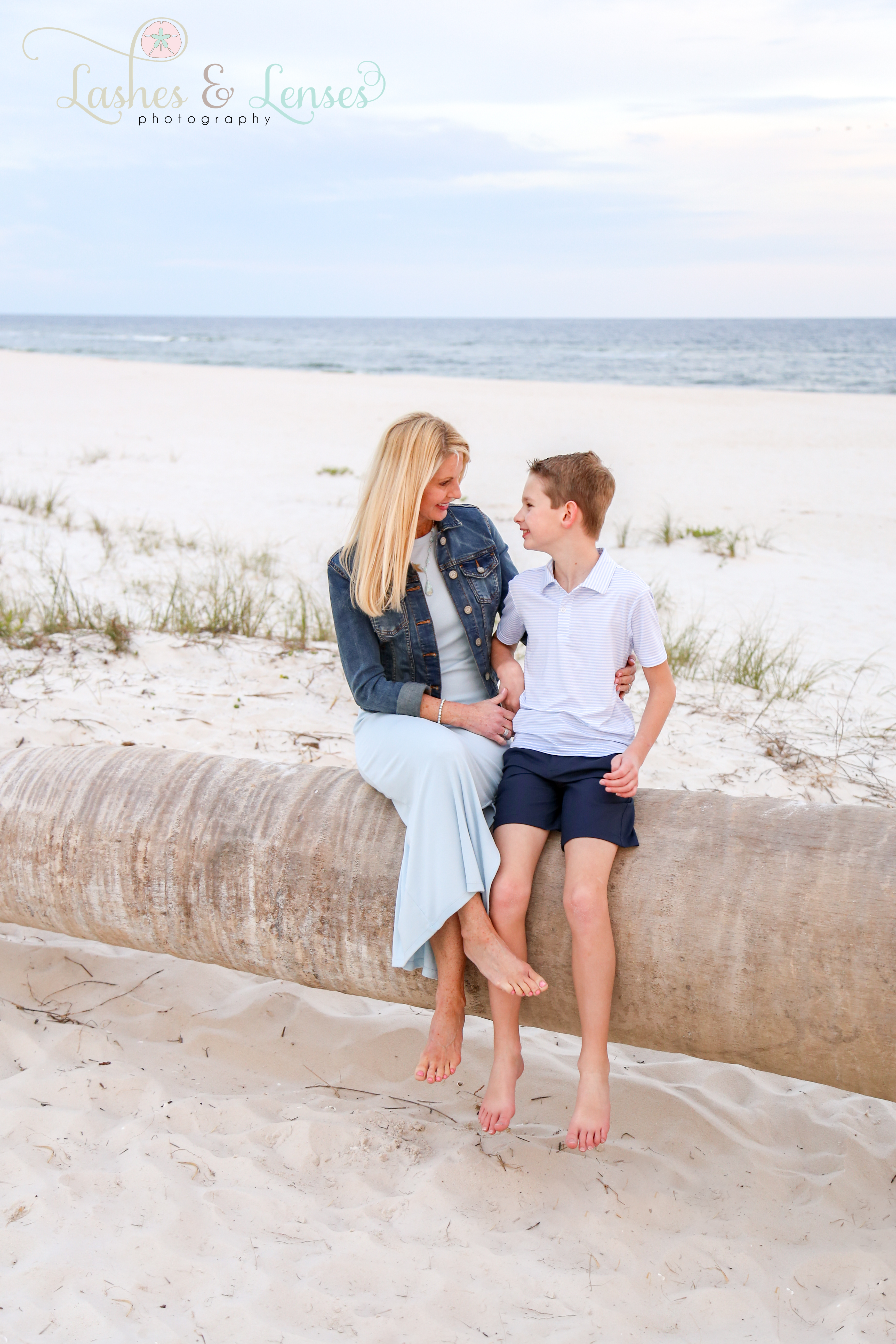 Mom and son sitting on washed up palm tree on the beach at Johnsons Beach in Perdido Key