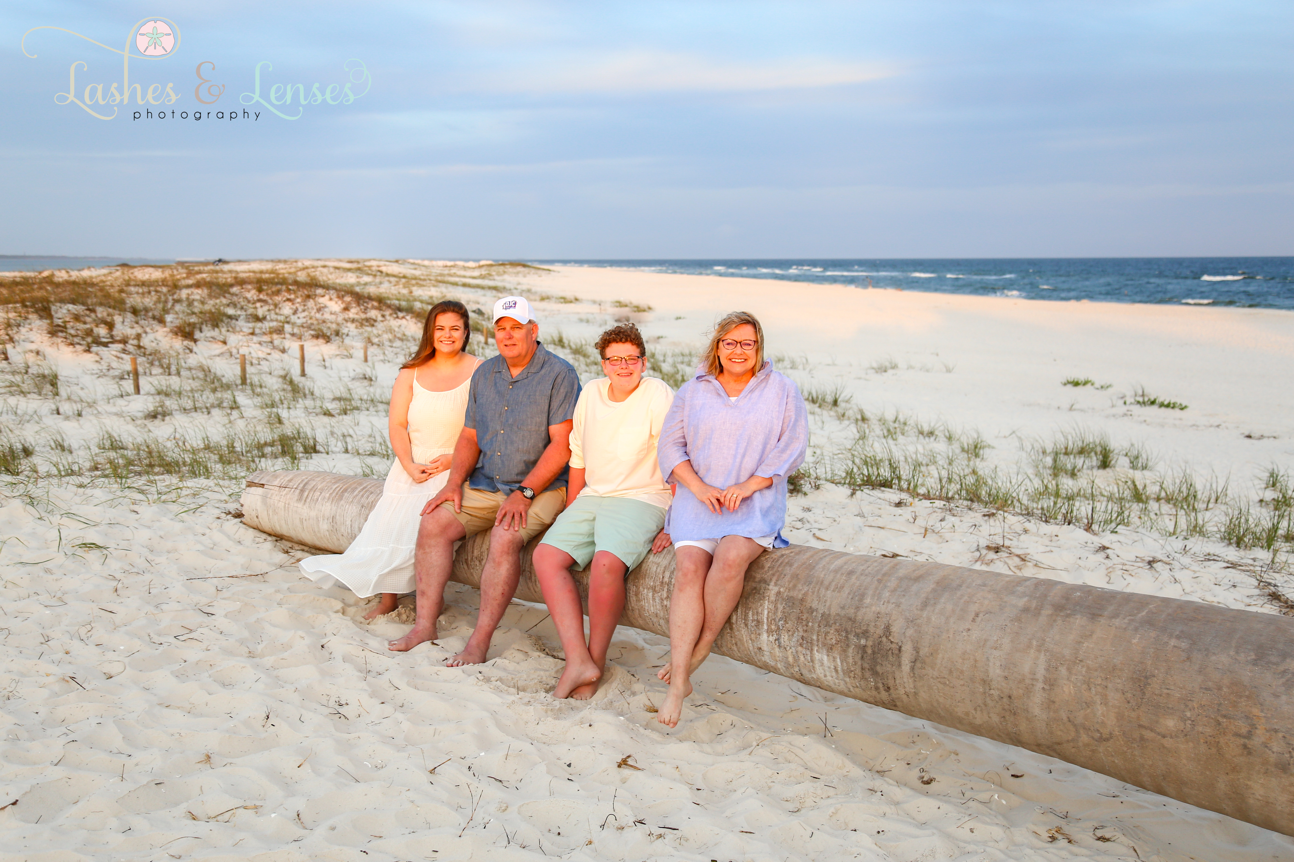 Mom and Dad with their two teen children sitting on a washed up log on the beach at Johnsons Beach in Perdido Key