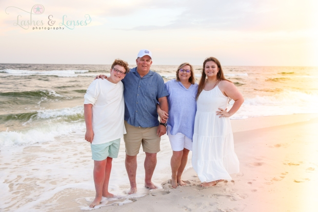 Parents with teen daughter and son standing next to the water at Johnsons Beach in Perdido Key