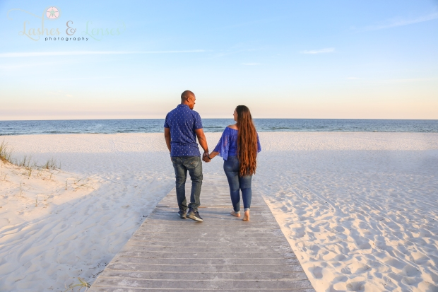 Couple walking hand in hand on the boardwalk towards the water at Johnsons Beach in Perdido Key