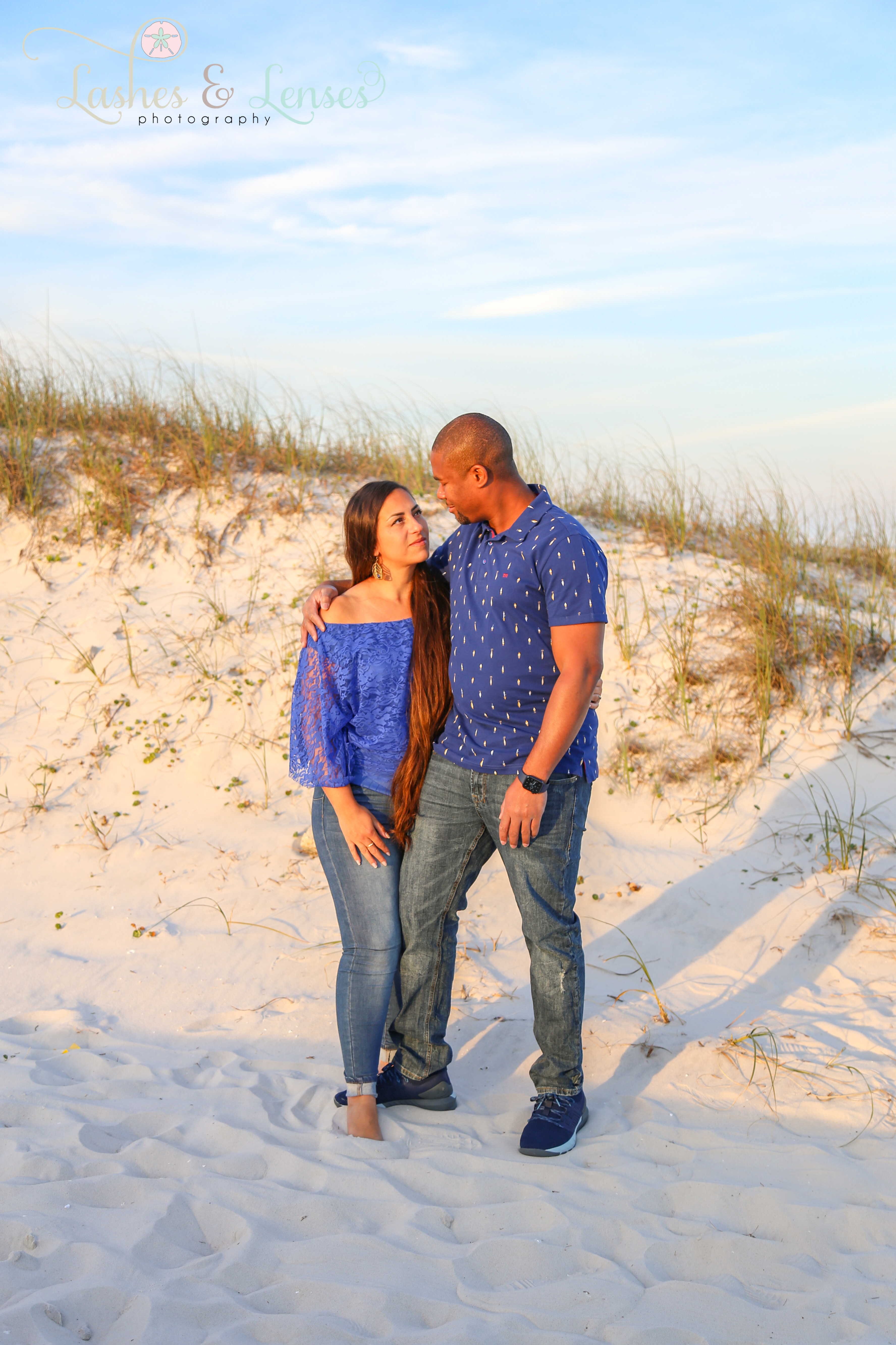 Couple in blue shirts and blue jeans looking at each other on the boardwalk at Johnsons Beach in Perdido Key