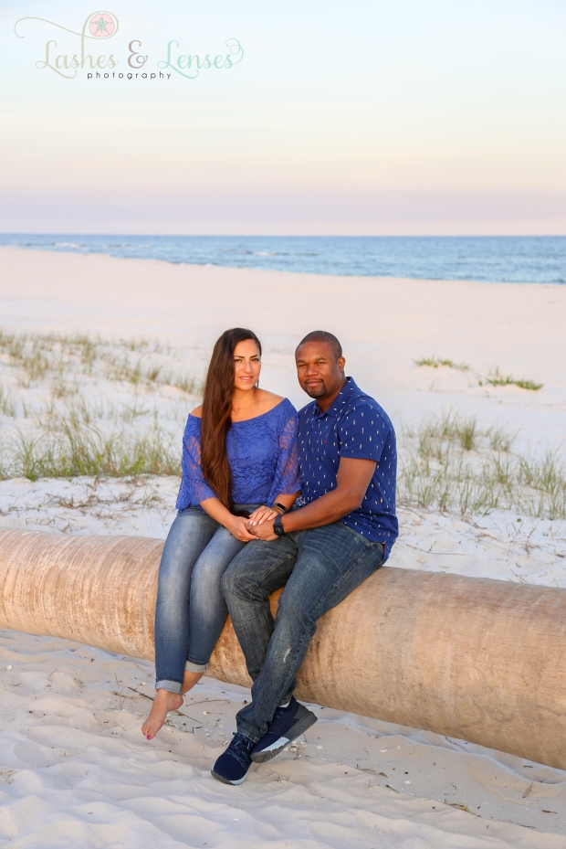 Couple sitting on a washed up palm tree at Johnsons Beach in Perdido Key