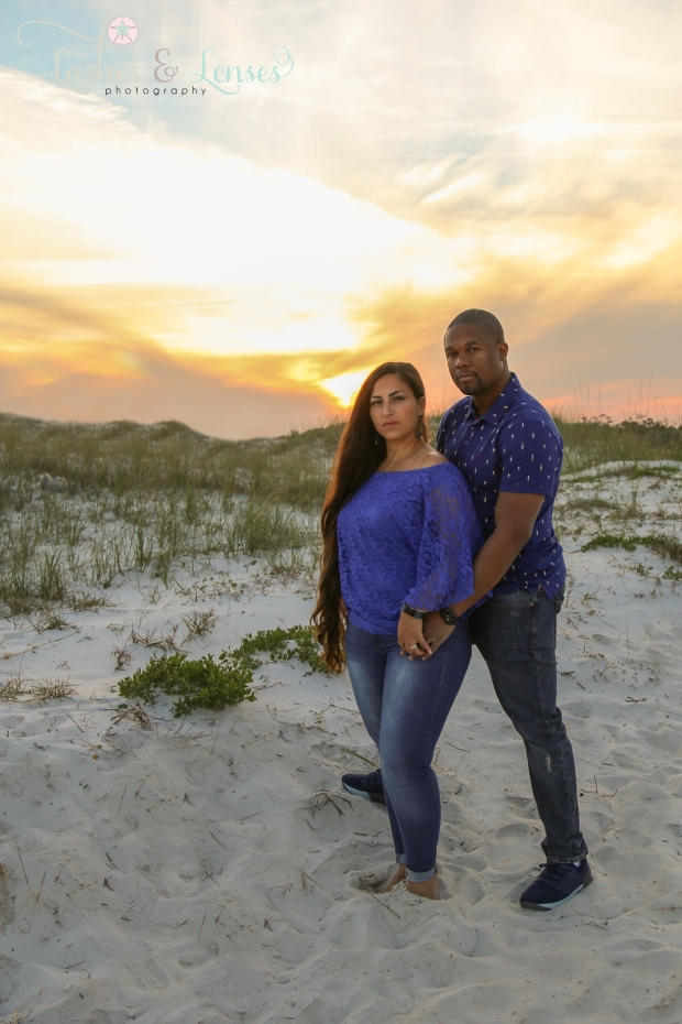 Couple standing by the sand dunes with the sunset behind them at Johnsons Beach in Perdido Key