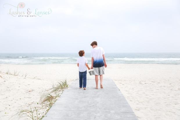 Boy cousins walking on the boardwalk towards the gulf at Johnsons Beach in Perdido Key