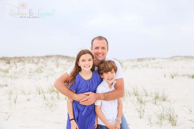 Dad with daughter and son standing in the sand dunes at Johnsons Beach in Perdido Key