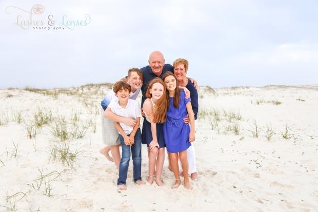Grandparents hugging grandchildren on the beach at Johnsons Beach in Perdido Key