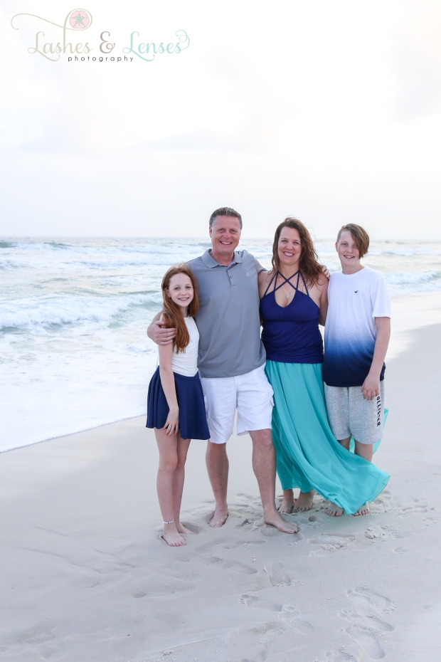 Mom and Dad with son and daughter standing next to the water at Johnsons Beach in Perdido Key