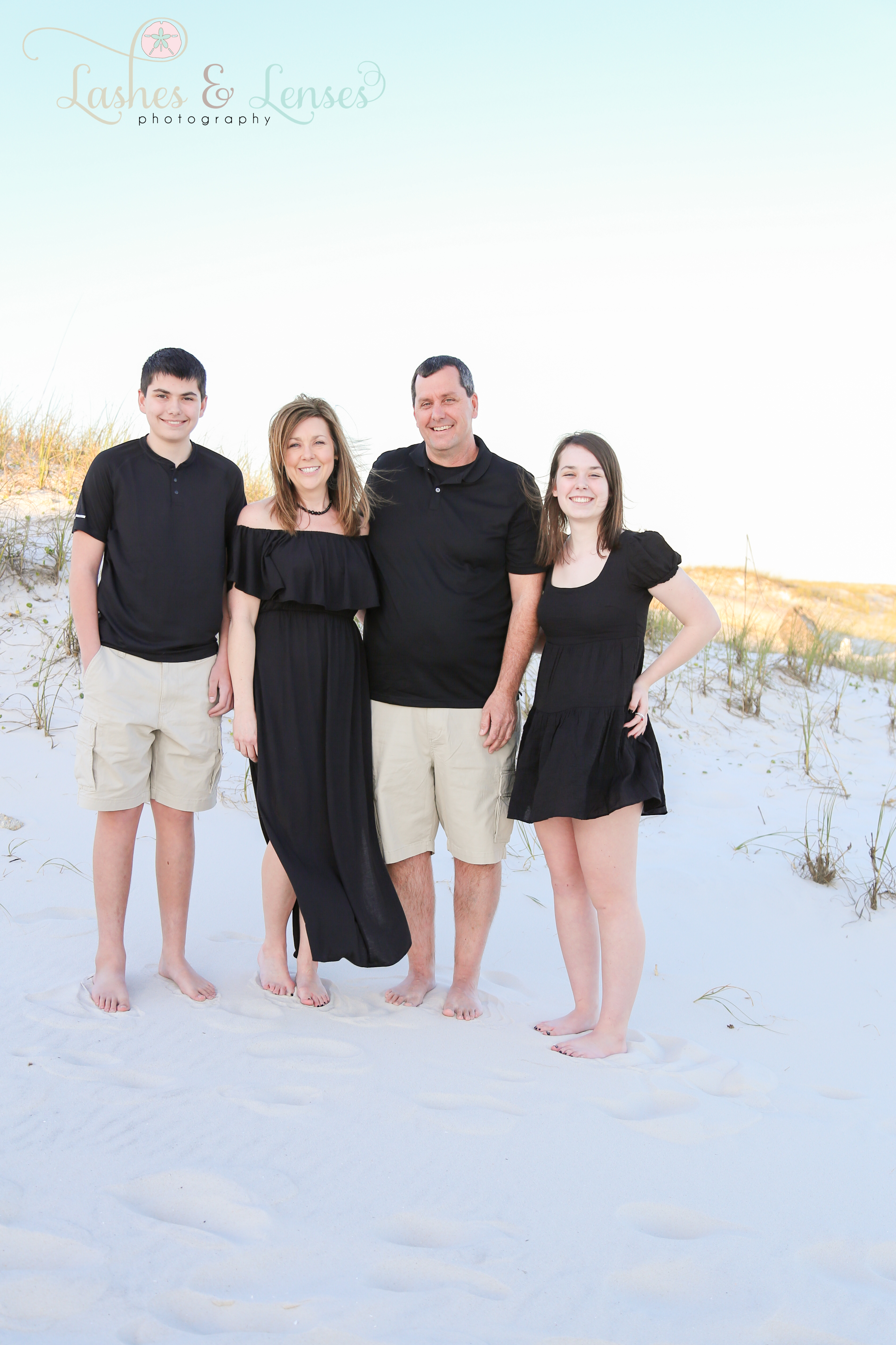 Family standing next to the sand dunes at Johnsons Beach in Perdido Key