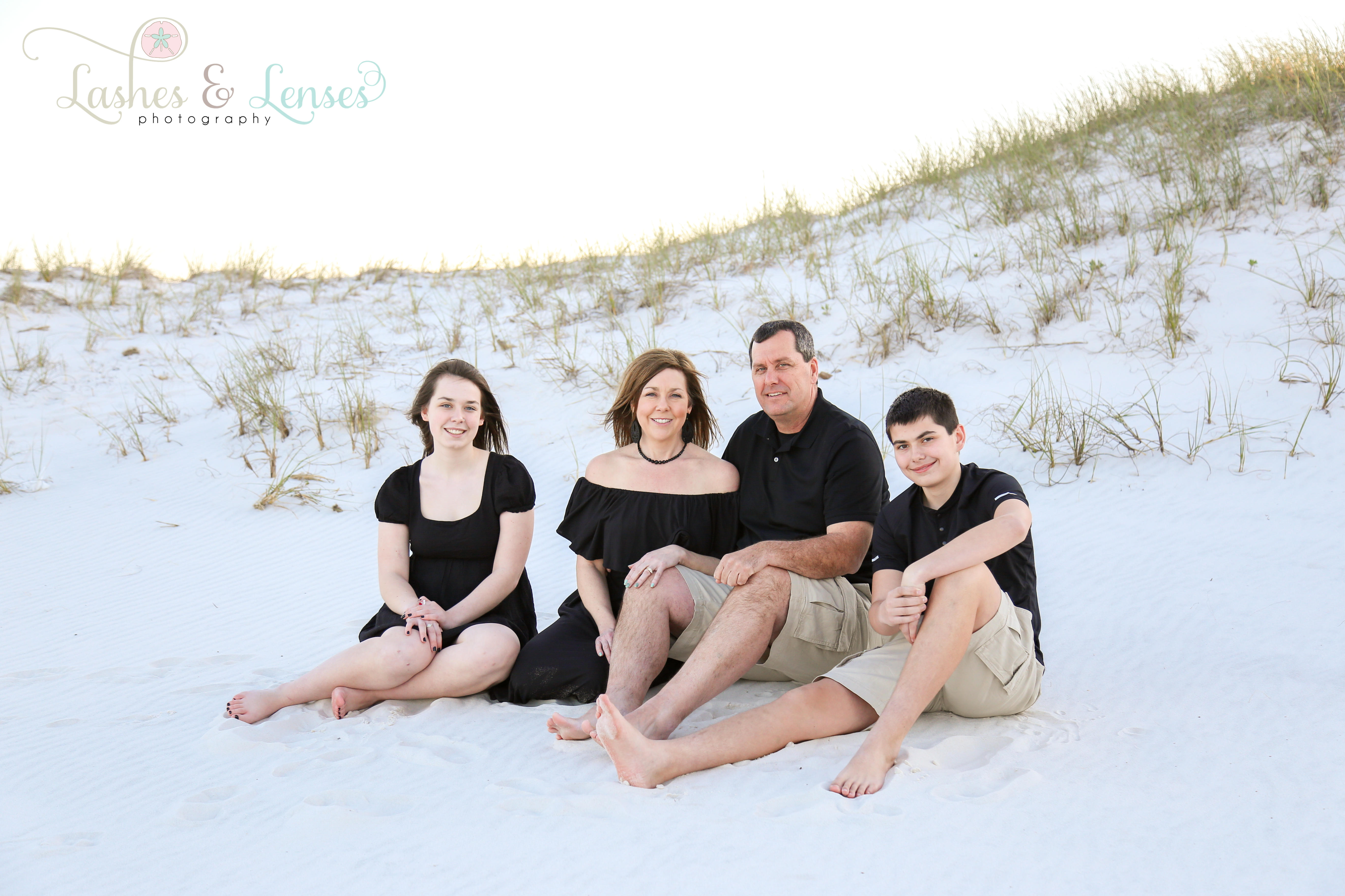 Mom and Dad sitting in the sand with their son and daughter at Johnsons Beach in Perdido Key