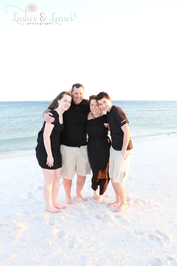 Mom and Dad hugging their teen kids next to the water at Johnsons Beach in Perdido Key